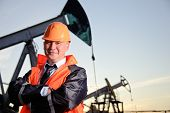 stock photo of blue-collar-worker  - Oil worker in orange uniform and helmet on of background the pump jack and sunset sky - JPG