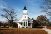stock photo of sanctification  - small white church with steeple blue sky in background - JPG