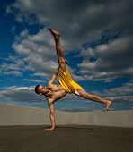 Tricking On Street. Martial Arts. Man Kick With Hand Support Barefoot. Taken From Low Angle Against  poster
