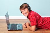 Photo of a boy wearing headphones looking towards camera lying on the floor next to his laptop computer.