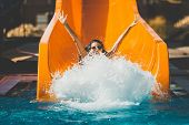 Joyful Woman Going Down On The Rubber Ring By The Orange Slide Make The Water Splashing In The Aqua  poster