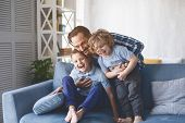 Portrait Of Laughing Dad Hugging Beaming Kids Having Entertainment On Sofa In Living Room. Satisfied poster