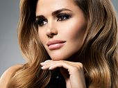 Closeup portrait with a pretty female face. Beautiful young woman with long brown hair.  Fashion mod poster