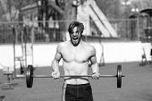 Sportsman Lift Barbell On Stadium. Man With Athletic Torso, Strong Arms. Athlete Shout Training With poster