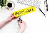 Make The Impossible Possible. Cutting The Part Im Of Written Word Impossible By Sciccors. White Back poster