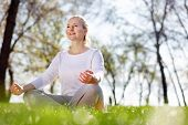 So Peaceful. Cheerful Peaceful Woman Sitting In The Grass While Meditating poster