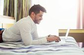 Arabic Businessman Lying On Bed In Hotel And Using Laptop. Smiling Man Working In Hotel Room And Typ poster