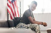 Female Army Soldier In Camouflage Clothes Sitting On Sofa poster