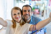 Smiling Middle-aged Couple Taking Selfie Photo In Mall And Looking At Camera With Blurred View In Ba poster