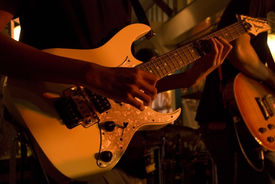 picture of ibanez  - A musician playing an electric guitar at a night time concert  - JPG