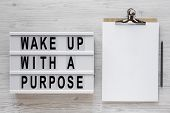 wake Up With A Purpose Words On A Lightbox, Clipboard With Blank Sheet Of Paper On A White Wooden  poster