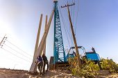 Pile Driving Working At Construction Site. Hydraulic Drilling Machines For Piling Into Ground. poster