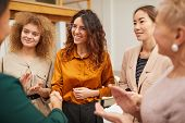 Group Of Friendly Women Clapping Hands And Congratulating Their Colleague On Getting Career Promotio poster