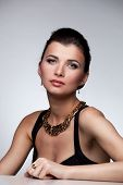Portrait of luxury woman in exclusive jewelry and black dress