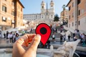 closeup of the hand of a caucasian man holding a red marker at the famous Piazza di Spagna square, a poster