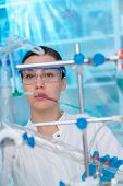 Young woman in chemical lab Young woman in chemical lab. cience professional pipetting solution into poster