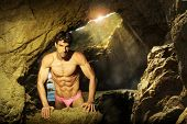 Sexy fit shirtless male model posing in beautiful cave setting with light streaming in
