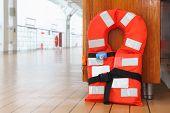 Singular orange life jacket stands on deck of cruise passenger liner; close up