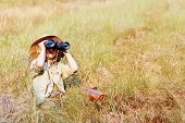 Young boy plays safari explorer with binoculars and bush hat in a field. happy adventure seeking kid