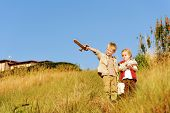 Young children playing explorers with treasure map and wooden sword. little adventure seeking kids h
