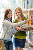 Two female teenage girls looking for book in school library