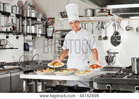 Постер, плакат: Портрет уверенно мужской шеф повара представляя макаронные блюда в коммерческих кухне счетчик, холст на подрамнике