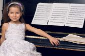 little girl in a beautiful dress sits at the piano