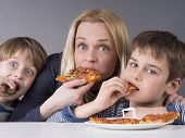 Hungry family, mother and son eating pizza, younger kid prefers strawberries