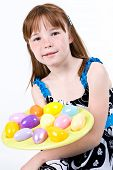 Young female child holding a plate of Easter eggs