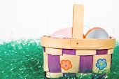 Easter basket with colorful Easter eggs sitting in artificial grass
