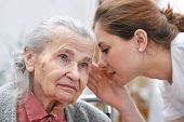 stock photo of gratitude  - Female nurse is speaking in senior woman ear - JPG