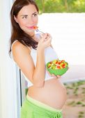 Beautiful expectant girl eat fresh vegetable salad, pregnant model at home, healthy pregnancy concept