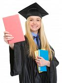 Smiling Young Woman In Graduation Gown Showing Book