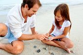 pic of daddy  - Father and daughter day at the beach collecting shells together having fun and smiling - JPG