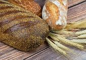 Assorted Bread And Wheat Ears On Wooden Background