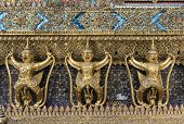foto of garuda  - A line of a fight between Garuda and Nagaone of beautiful guardian sculptures around the chapel of the temple of the Emerald Buddha