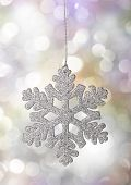 Christmas snowflake ornament on a holiday lights background