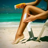 foto of sun tan lotion  - Tan woman applying sun protection lotion - JPG
