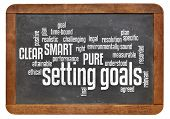cloud of words or tags related to setting goals and SMART, PURE and CLEAR methods on a  vintage slat
