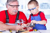 stock photo of grandfather  - Grandfather and grandchild working together in garage - JPG