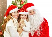 Picture of happy family celebrating New Year eve, little baby girl with parents enjoying winter holidays, father wearing red Santa Claus costume, Christmas magic, happiness and love concept