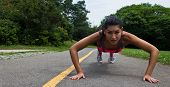 Fit Young Woman Doing Push-ups Outdoors