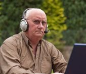 Voip Senior Male Laptop And Headphones