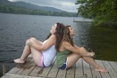 Two Teenage Girls On Dock Sitting Back To Back, Laughing