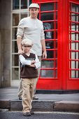 Happy father and son outdoors by red phone booth