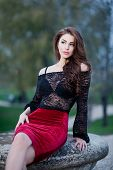 Charming young brunette woman in black lace blouse and red skirt sitting on rock. Sexy gorgeous girl