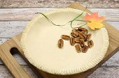 image of pecan  - Holiday festive baking with an empty pie shell pastry crust with raw pecan nuts ingredients and autumn leaf decoration - JPG