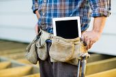stock photo of leather tool  - Midsection of construction worker with tablet computer in toolbelt at site - JPG