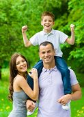 Happy family of three. Dad keeps son on shoulders. Concept of happy family relations and carefree le