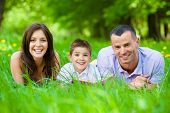 Happy family of three lying on grass while reading book. Concept of happy family relations and carefree leisure time